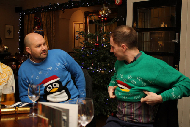 Two men in a bar wearing highly decorated 'Christmas' jumpers