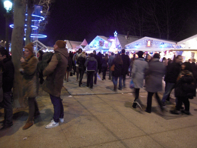 Members of public walking between stalls at the Christmas Market on Paris's Champs-Elysee