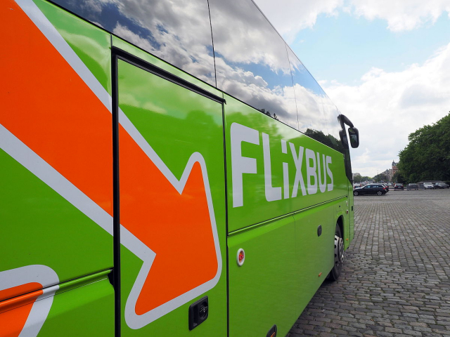 A photograph looking along the side of a green-liveried Flixbus coach