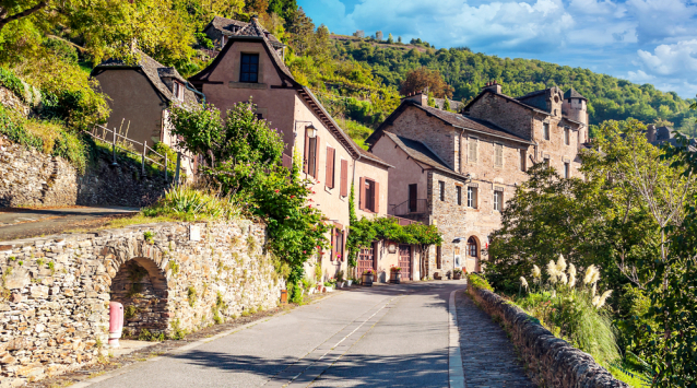 a rural French schene with road and houses and trees