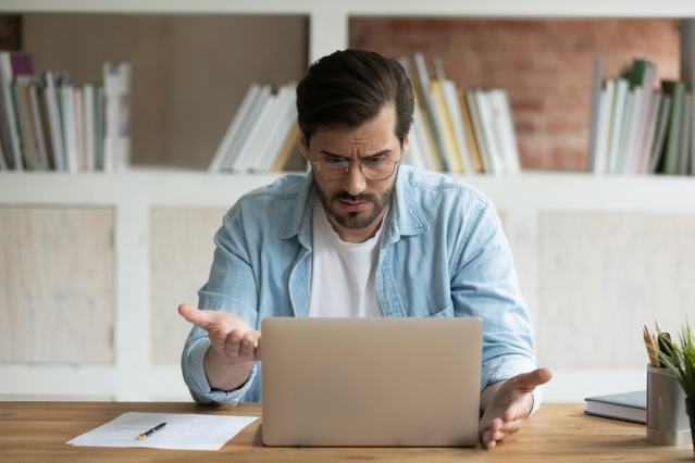 Man looks at computer in frustration