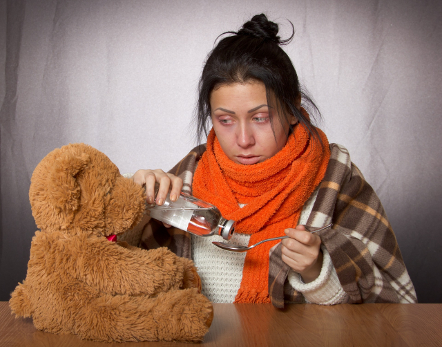 A young women who is clearly ill pours medicine into a spoon