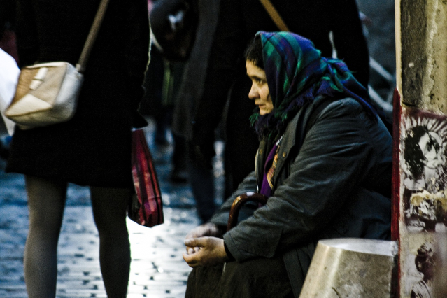 Homeless woman sitting down at the side of a street as people walk by