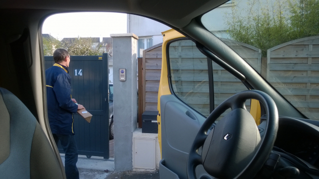 A view from inside a La Poste vehicle of a French postal worker delivering a parcel to a private property