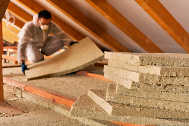 A man installing thermal insulation layer under the roof - using mineral wool panels as part of a home improvement or renovation project