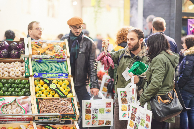 people standing beside a fruit and vegetable stall at a market