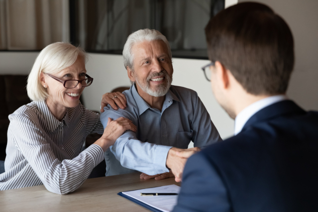 An older couple smiling as they arrange a deal with a lawyer