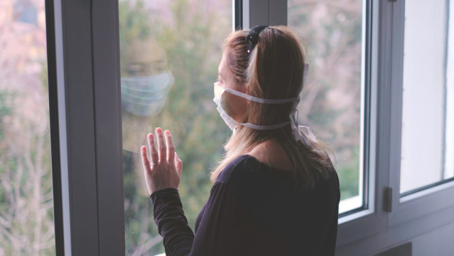 woman in mask looks out of window