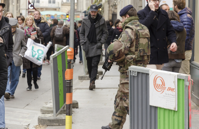 An armed soldier patrols a busy French street