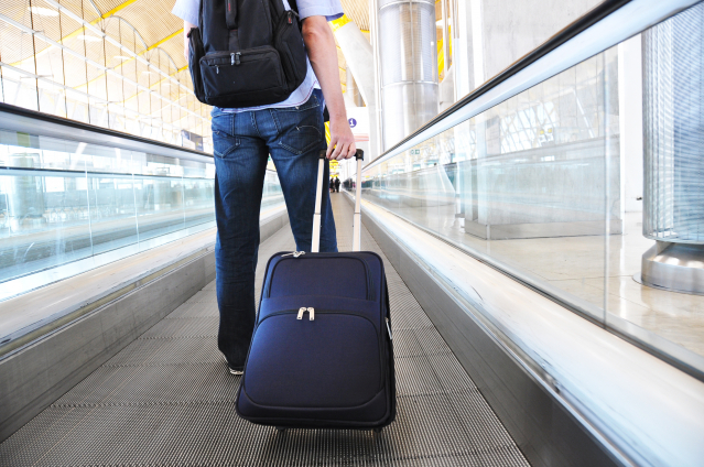 Man walking with suitcase on airport walkway