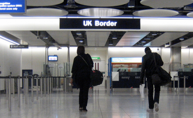 Two people arrive at UK border control at an airport