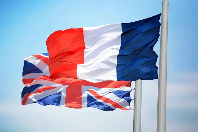 The French and British flags against a blue sky