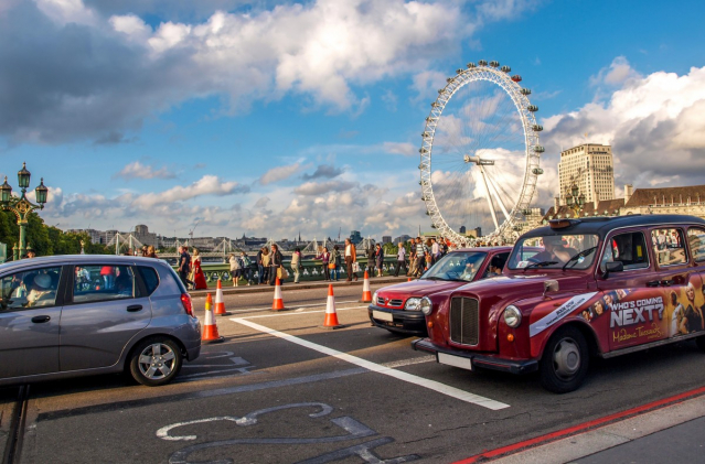 A London street scene including a taxi and the London Eye
