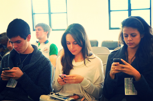 Three young people sitting alongside each other, all using a smartphone