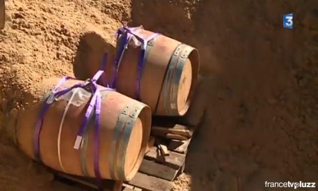Two barrels half-buried in sand, lying on wooden slats