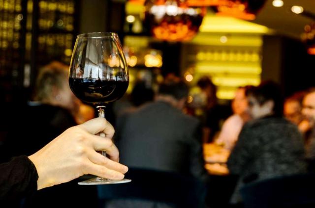 hand holding glass of wine against dark background