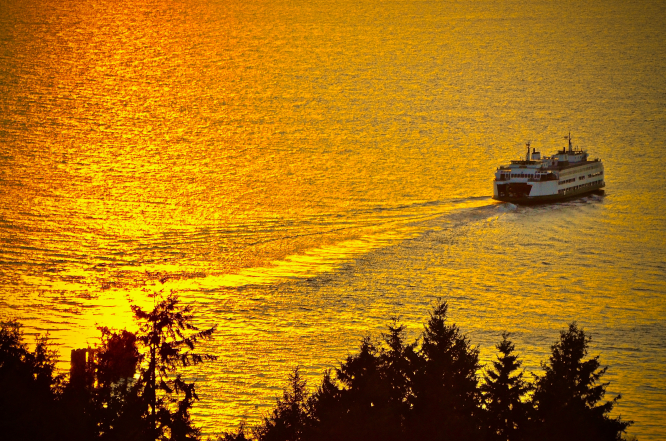 A ferry sails over golden water in West Seattle, United States.