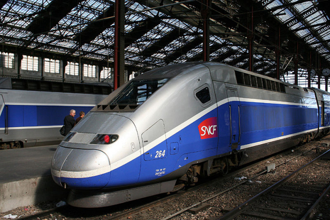 A blue and grey TGV sits at a platform