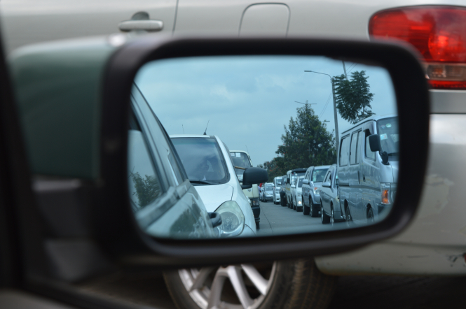 A car wing mirror showing heavy traffic. France will open its first carpool lane near Grenoble today (September 30)
