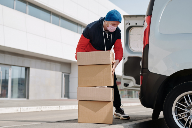 A delivery man loading boxes into a van. Influential French figures unite against Amazon