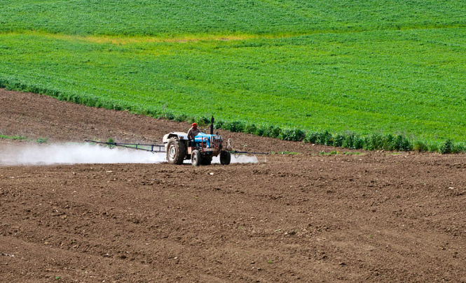 A farmer spraying chemicals on a field. French mayors ban use of pesticides on farms under local law