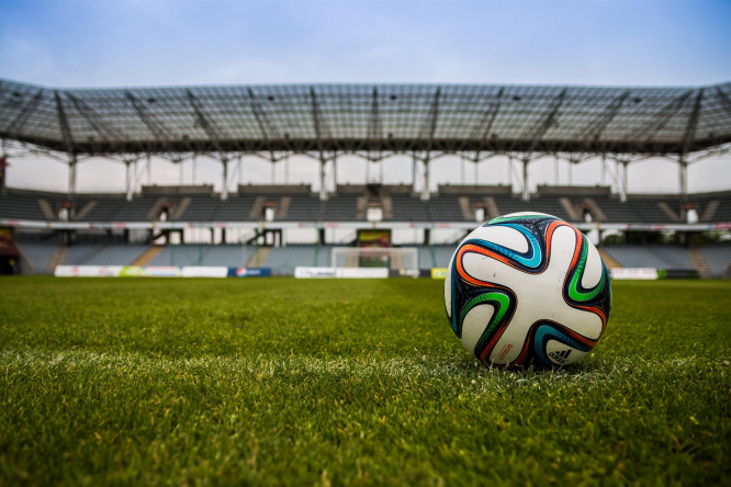 A football on the grass in a stadium. President announces support for sports in France