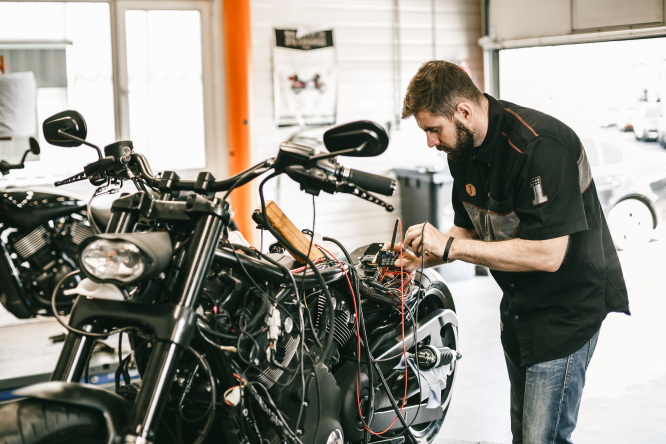 An image of a man repairing a motorbike in a garage