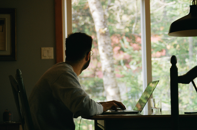 A man looks out of the window while working from home. France Covid-19: No plans for third lockdown 'at this stage'