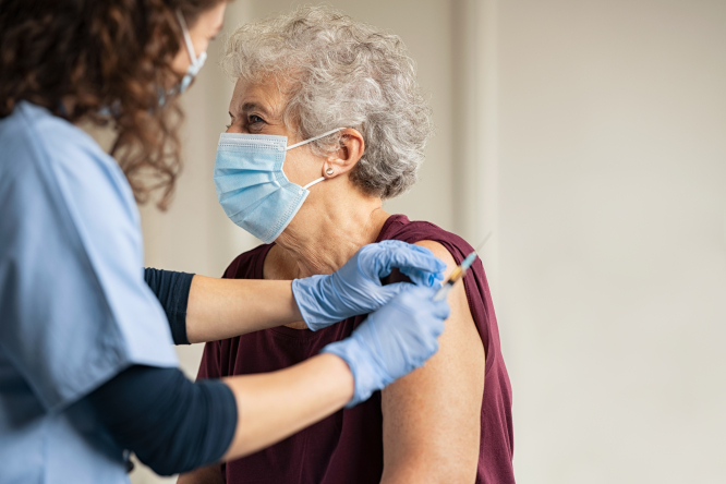 Image of a lady being vaccinated against Covid-19 by a doctor.