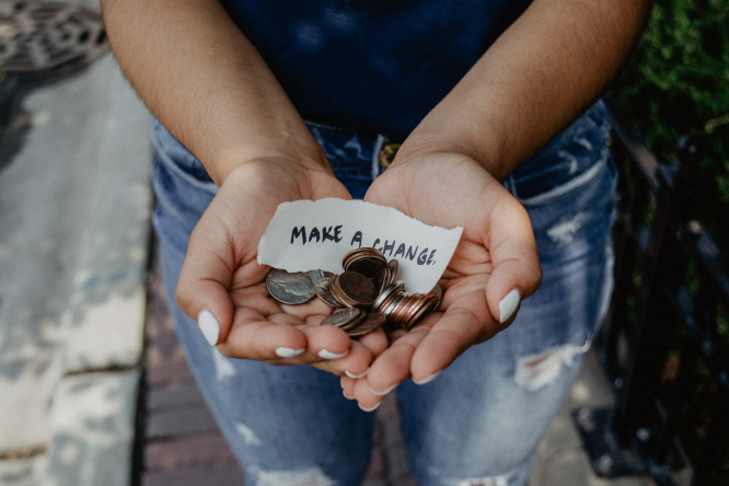 Person showing both hands with coins inside. A note reads, 'change for change'. Article: we answer a question from The Connexion Help Guide on inheritance law and wills in France: how can I leave money to a charity? Photo by Kat Yukawa / Unsplash