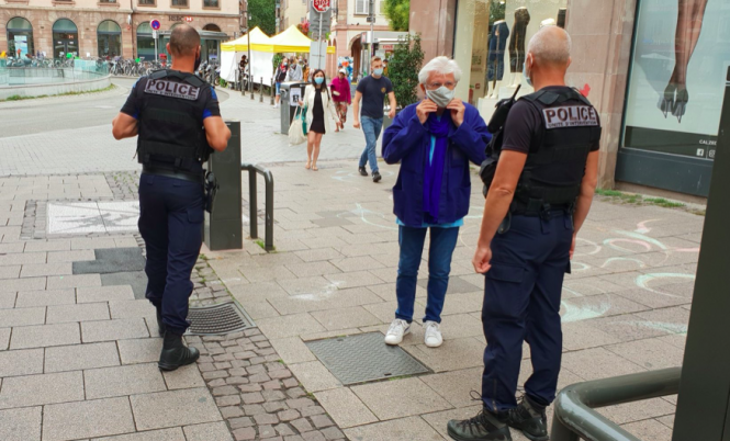 A woman wearing a mask with police in Strasbourg. A rule enforcing mask-wearing in all public places in the Bas-Rhin department has been challenged in French court.