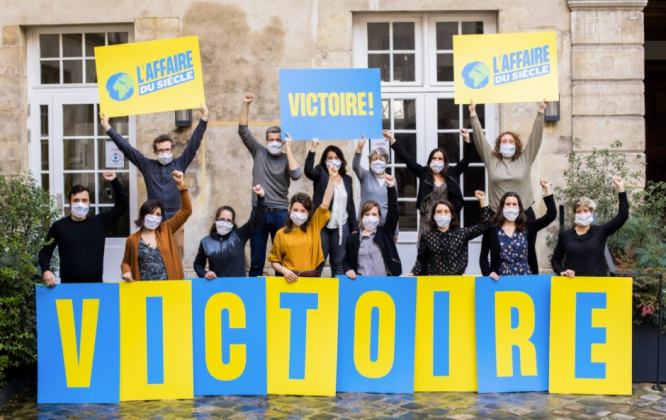 NGO members hold up victory signs. France ordered to pay compensation for 'climate inaction'
