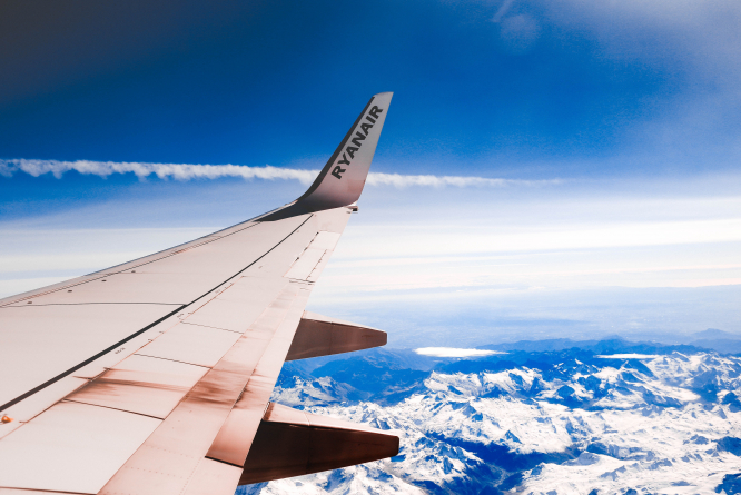White Ryain airplane wing in a blue and cloudy sky. Article: Airlines still owe customers refunds for cancelled flights - what are the airlines saying? Photo by Anastasia Dulgier / Unsplash