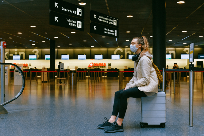 A woman in a mask waiting at the airport. Airlines told to enforce French Covid-19 border closure