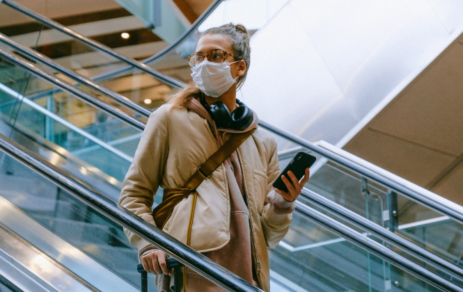 A woman on an airport escalator wearing a mask. France introduces Covid tests for 'at risk' airport arrivals