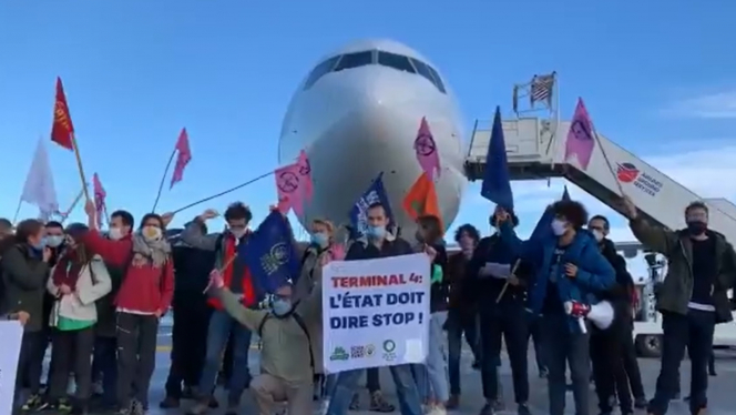 Protesters hold banners and placards at Roissy airport. Arrests at Paris Roissy-CDG after air traffic protests against expansion of air travel and T4 project