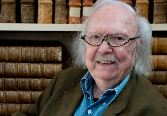 The late Alain Rey sits with a book next to a bookcase. French linguist Alain Rey dies aged 92