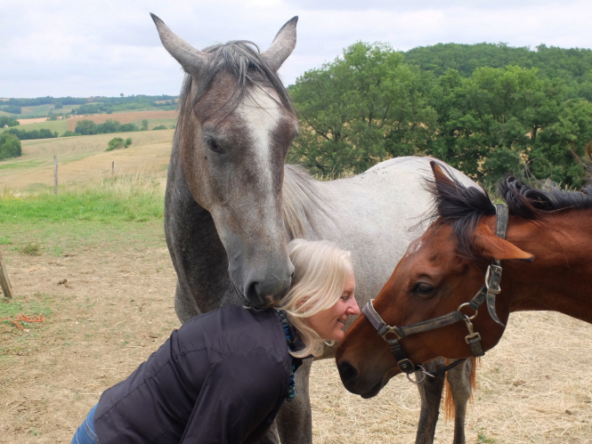 Blonde woman is nuzzled by her horses, one grey and a chestnut with open countryside behind them