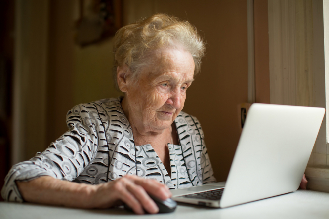 An elderly woman using a computer. People vaccinated early struggle to get QR code for French health pass