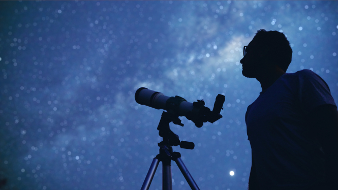 Astronomer looking up at the night sky with telescope