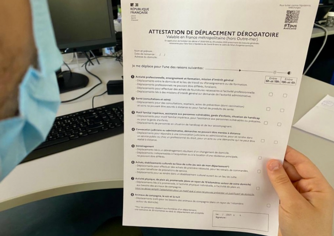 A man holds a new attestation form. Travel distances and link to forms for new 10km lockdown in France