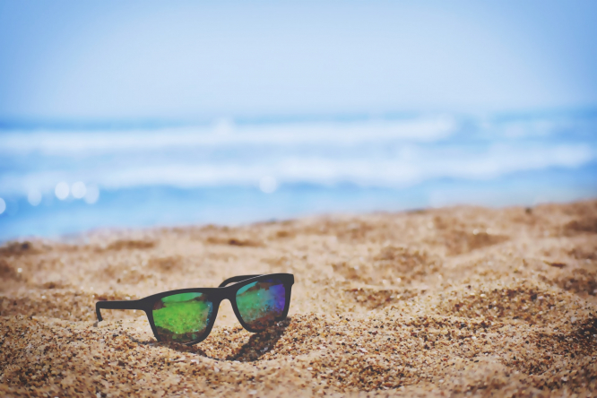 Sunglasses on the sand on a sunny beach. France has lost €30-40 million from lack of summer tourists in 2020