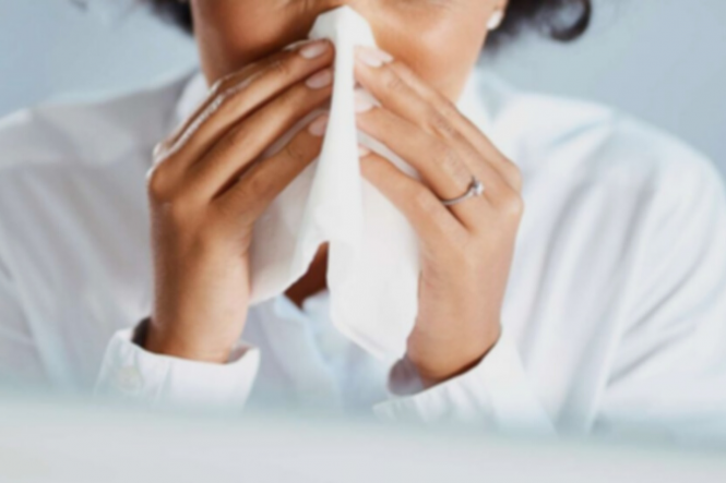 A woman blows her nose. New French nose spray eliminates 99% of Covid virus