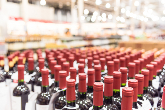 Bottles of wine lined up in stockroom. French winemaker's relief as EU-US deal removes export tariffs