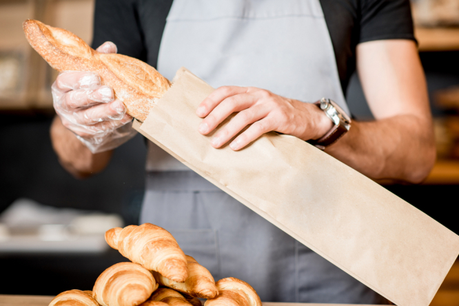 A baker puts a baguette in a paper bag. Should France allow bread to be sold seven days a week?
