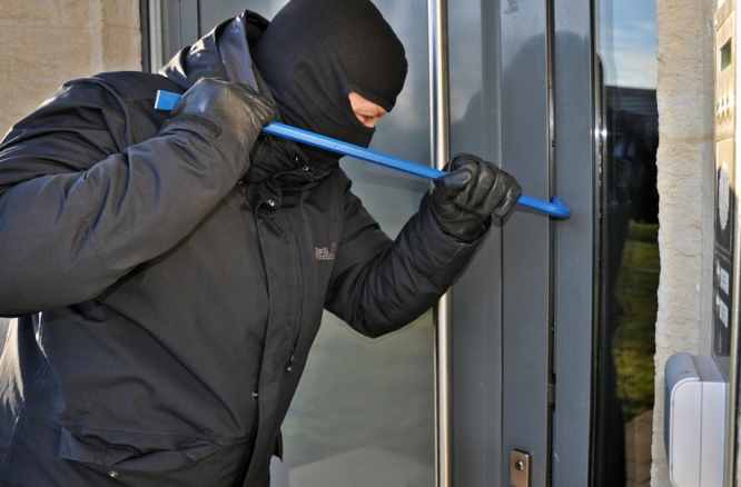 A burglar attempting to break in. French police holiday home surveillance service in demand as break-ins soar