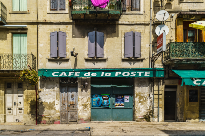 A closed cafe on a dilapidated street in Sommières, France. Why are French city centres attracting fewer visitors?