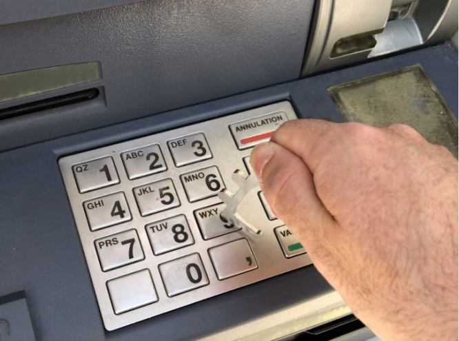 A man uses a hook to key in on an ATM. Fewer ATMs in France amid Covid, online, and cashless trends
