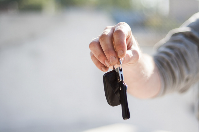 A man handing over some car keys. Hire car shortage in France ahead of post-lockdown summer 2021