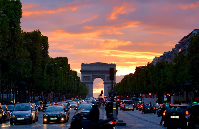 Cars driving down the Champs Elysées. French Covid rules have shrinking impact on cutting travel